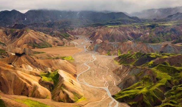 a-river-system-running-between-orange-and-green-rhyolite-mountains-in-landmannalaugar-4